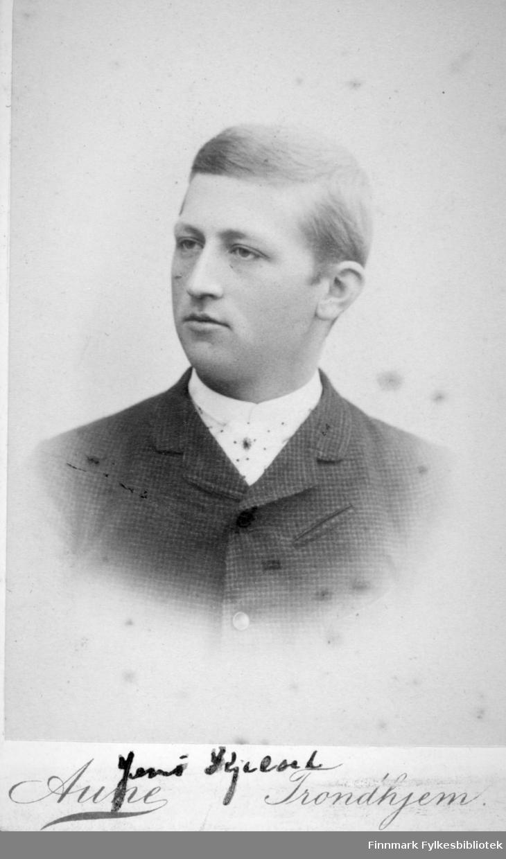 Portrett av en mann iført en mørk dressjakke og hvit skjorte