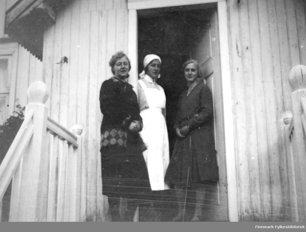 Tre damer står i inngangspartiet/vindfanget til et hus. Døren står delvis åpen og vindfanget har stående panel med et hvitmalt trapperekkverk. Det står kuler på hver stolpe til gelenderet. Helt til venstre ses deler av et vindu og en høy plante ved veggen. De to damene på sidene har mørke kjoler, hun til venstre med et belte eller sirkelmønster rundt hoftene. Hun i midten har en lysere kjole, hvitt forkle og tørkle på hodet.