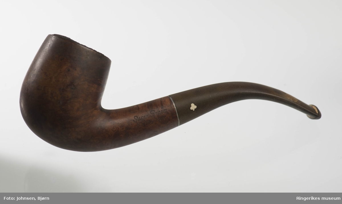Sylinderformet pipehode med fordypning og rør i bunnen, formet og svunget munnstykke med liten tverrgående åpning. To deler som er sammenføyd, overgangen markert med en smal metall//sølvring.