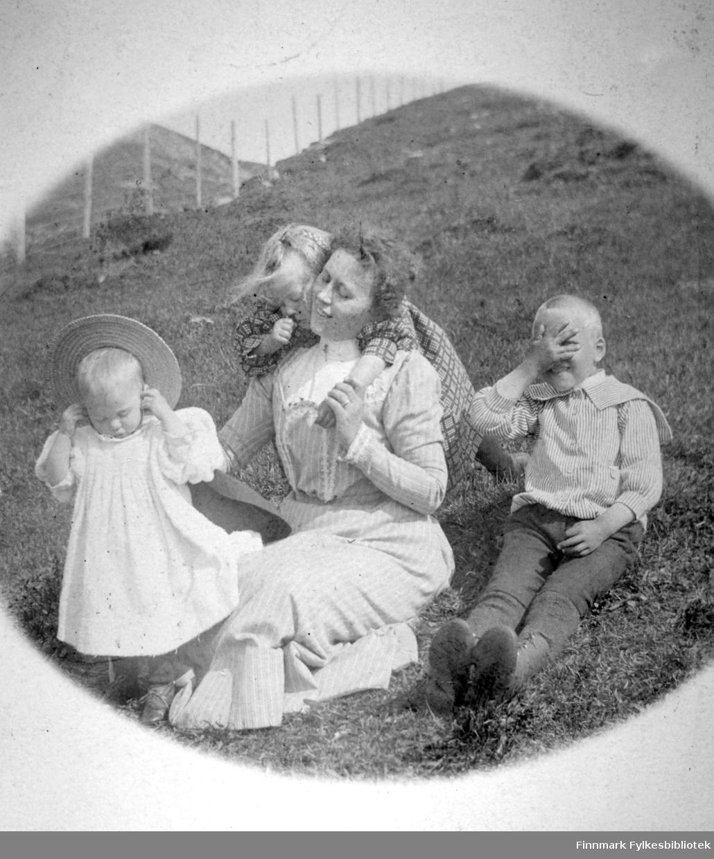 En dame i langt, lyst, stripete skjørt og en litt mørkere overdel sitter sammen med tre barn i en lyng- og gressdekt skråning. Det minste barnet, til venstre, har et lys kjole med puff-ermer og en stråhatt på hodet. Jenta som henger over skuldrene til dama har en rutet kjole. Gutten til høyre har mørke sko/støvler, mørk bukse og en lys, stripet skjorte på seg. Det er en ganske bratt skråning der de sitter og videre oppover. Et gjerde bestående av stokker og netting, går oppover bakken til venstre.