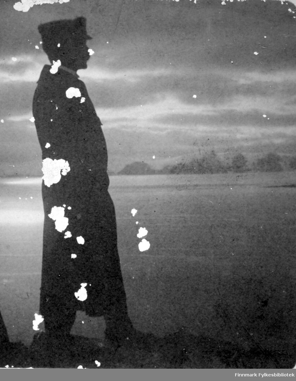 En mann poserer foran sjøen. Han har en lue på seg, muligens en uniformslue. En lang mørk frakk, mørke bukser og sko. En hvit skjortekrave ses såvidt i halsen. Havområdet i bakgrunnen ligger blikkstille og sola speiler seg i vannet til venstre på bildet. På andre siden av vannet ligger en fjellkjede som har fått snø på toppene. En liten flik av et nes stikker ut i sjøen til høyre på bildet. Ganske mye skyer på himmelen selv om det ser ut som det er oppholdsvær. Bildet er muligens tatt i Hammerfest.
