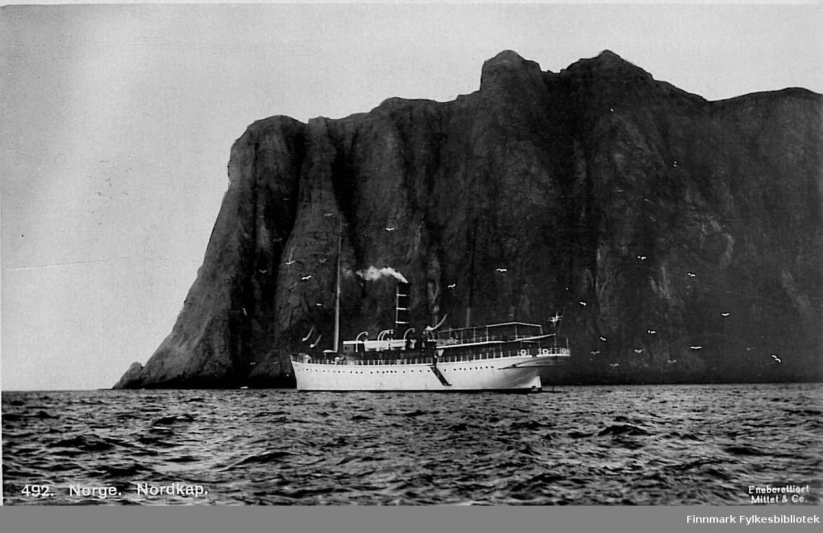 Postkort med motiv av et turistskip som passerer Nordkapp. Kortet er en julehilsen til Arthur Buck på Hasvik. Kortet er nok sendt rundt 1905-1910.