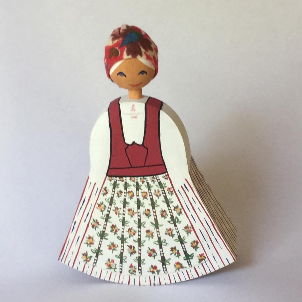 Docka av trä, dekormålad med svensk dräkt. Huvudbonad av mönstrat bomullstyg.