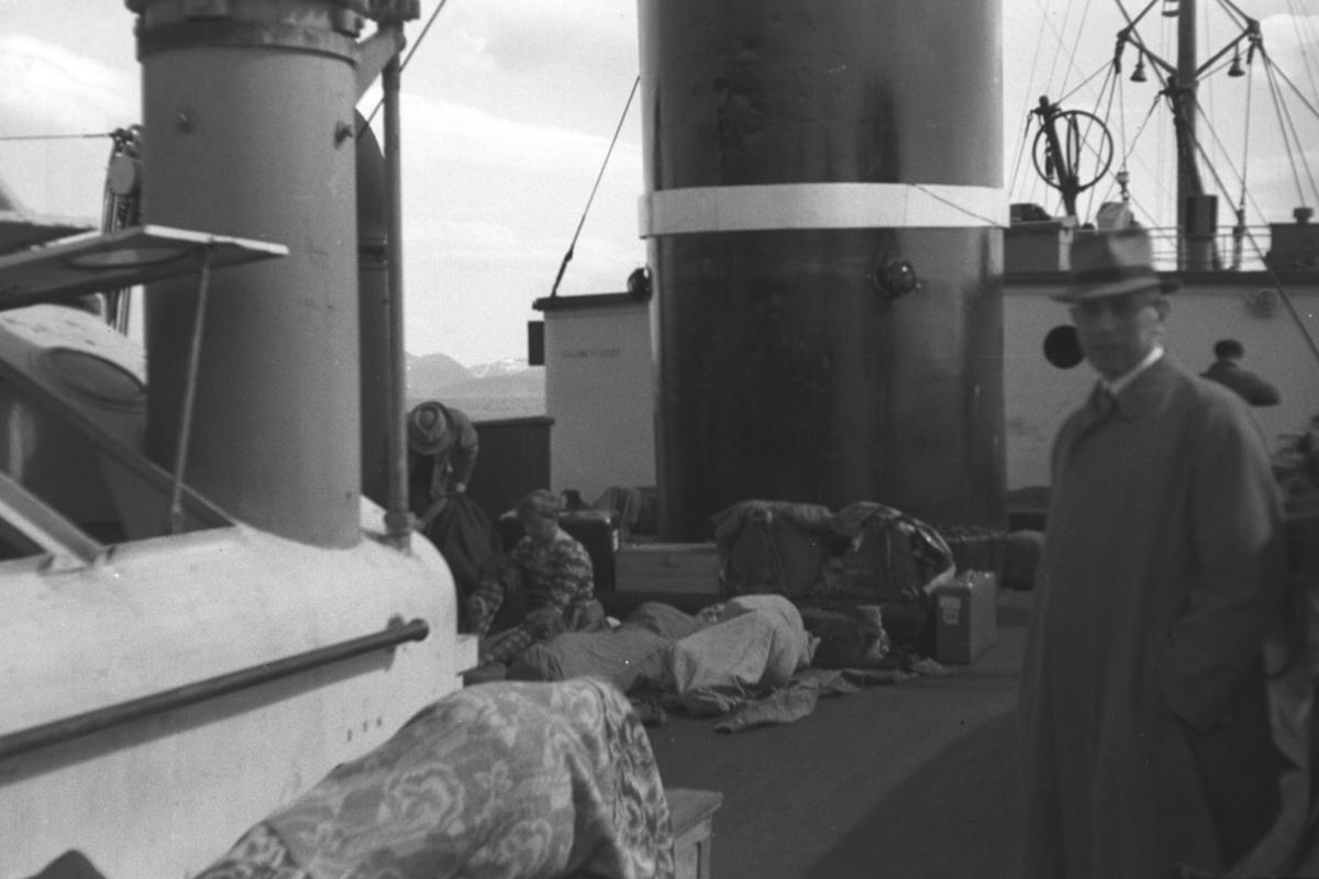 """En ukjent mann står på dekket til hurtigruteskipet D/S """"Nordstjernen"""". Mye bagasje ligger på dekket mellom han og skorsteinen."""
