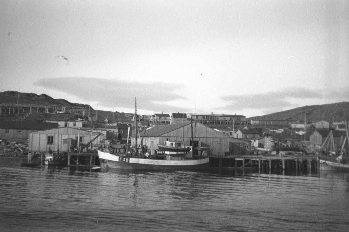 Bilde viser havneområde i Mehamn. Bildet er tatt i mai 1946. En fiskeskøyte ligger ved kai.
