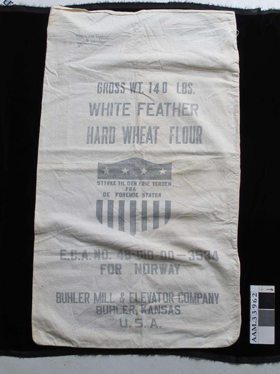 Sekk av bomull, lerretsbinding. Trykt tekst og emblem på ene side. Emballasjeprodusent, og vareleverandør er navngitt.