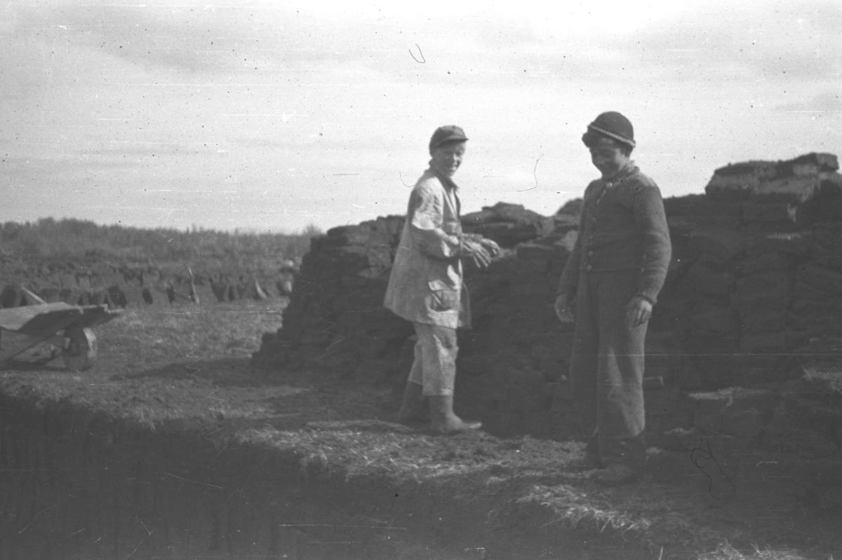 To gutter stabler torv til tørking i nærheten av Andersbymyrene. De er Tor Hauge til venstre på bildet og Odd Berg ved siden av.