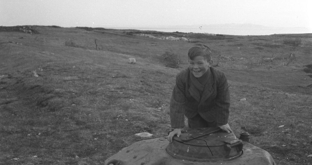 Øystein Hauge fotografert på Vadsøya like etter andre verdenskrig. Han lener seg mot et lokk som er et tårn fra en stridsvogn (stridvogntårnet er APX-R tårn til Renault R35/R40 og Hotchkiss H35/H39).