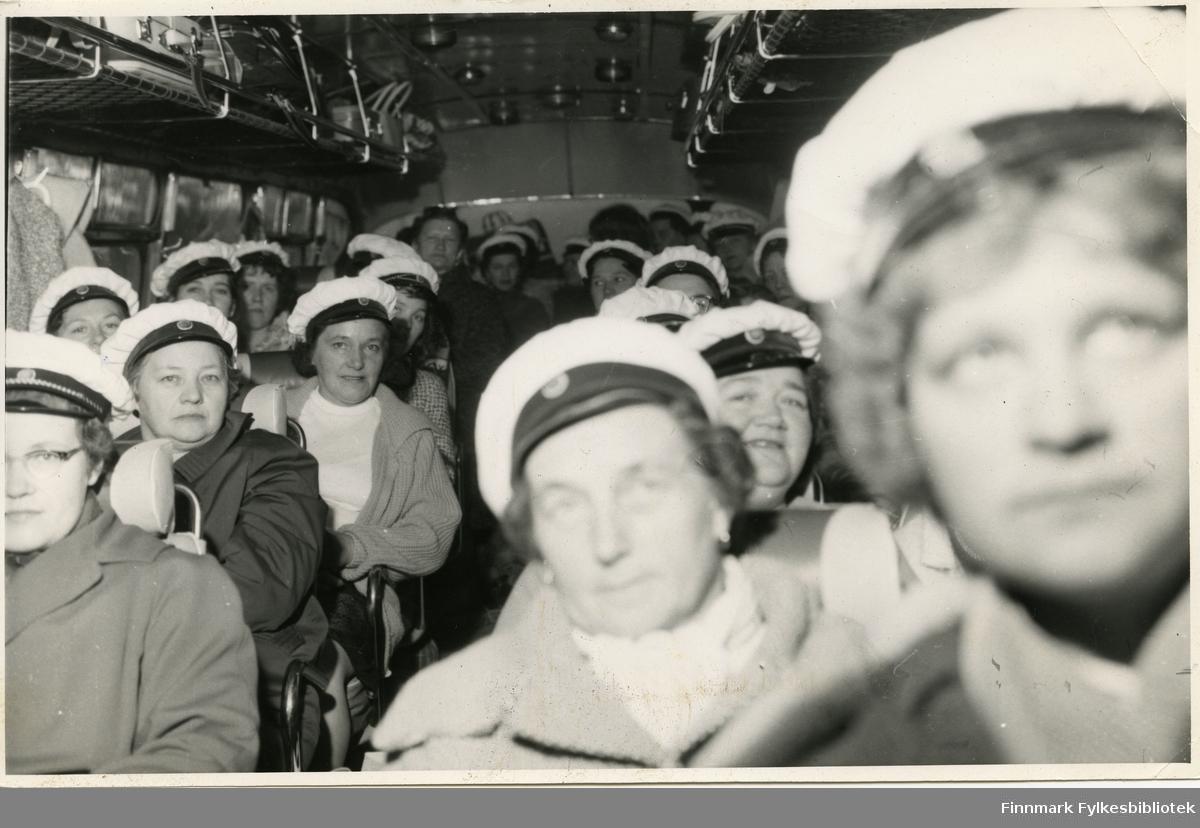 Vadsø damekor i bussen på tur til Berlevåg (muligens rundt 17. mai) 1962. Kvinnene har på seg en hvit hatt, trolig kor uniform. I bussens håndbagasje hylle kan man se vesker og kofferter av forskjellige slag. Damene har på seg jakker og gensere. Nederst i venstre hjørne: Ingrid Niskavara. Bak Bildet er det notert: 'M.Z', for Mimmi Zahl.