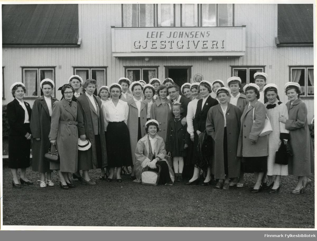 Bildet viser Vadsø damekor på sesongavslutning i Rustfjelbma 1952. Damene har vært på korstevne. Her står de foran Leif Johnsens Gjestgiveri. Huset har vinduer, i vinduene kan man se gardiner. Damene har på seg skjorte, skjørt og hatter. Enkelte bærer på vesker. Kvinnen som er nummer tre fra venstre (muligens Sigrid Hoel) har på seg briller. Flere av damene har på seg kåper. Karin Værnes som sitter på kne har på seg øredobber. Rekkefølgen på personene i bildet er noe uklart. Fra venstre: Bergljot (Bella) Stock, Ellen Høy, Sigrid Hoel, Pauline Stock, Alfhild Ballo, Aagot Olsen, Borghild Løkting, Mimmi Dallavara, Olga Jørgensen, Lisbeth (Lissi) Esbensen, (et amerikansk par), Mary Bohinen, Randi Hellander, Gunvor Holt, Klara Pettersen, Alfhild Bohinen, Hansine (Sina) Olsen, Astrid Karslen, Turid Bjørkli, Mimmi Zahl, Ruth Hågensen, Karin Værnes (på huk) og Småjenta Tove Hellander (Randi Hellanders datter). Tove har en sløyfe i håret.
