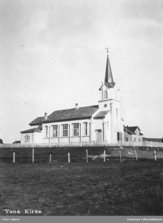 Postkort med Tana Kirke som motiv. På bildet kan man se gjerder som omringer kirkenområdet. På kirken kan ma se vindu, tak, dører og skorteiner.