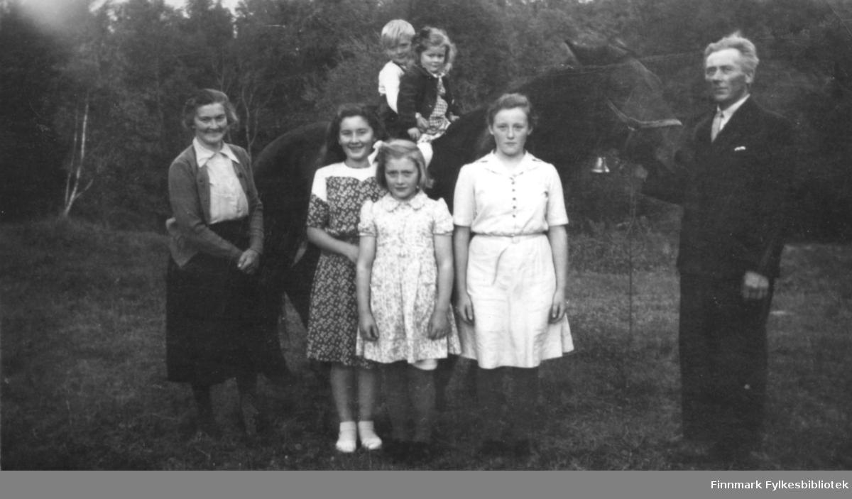 Hjemme på Gamnes hos familien Johansen i Tverrelvdalen. Familien flyttet hit etter at gården Fjellstad ble solgt i 1940. Fra venstre står mor Karen Thomine Lovise f. Kristensen, Karen Kristine g. Jakobsen, Anna Elisabeth g. Uglebakken, Ragnhild Marie g. Suhr og far Andreas Julius. Bakerst, oppe på ryggen til hesten Felix, sitter Johan Kristian og Åse Thomine g. Ingebrigtsen. Jentene foran er kledt i knelange kjoler. Far er kledt i en mørk dress, skjorte, og slips. Mor er kledt i skjørt og bluse med en jakke over. Johan Kristian har hvit skjorte, og søster Åse Thomine har kjole med en jakke over. Hesten har bissel, og en messing bjelle hengende under halsen. Andreas Julius kjøpte Felix på Krøderen. I 1953 ble den solgt til en mann i Karasjok, og ble brukt i tømmerskogen. I bakgrunnen av plassen hvor familien står, er det skog