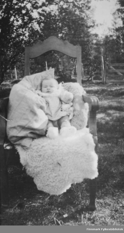 Giver av bildene Karen Kristine Jakobsen f. Johansen som sitter på et saueskinn, oppstøttet av puter i en stol. Stolen som står ute på bakken har utsjæringer. I bakgrunnen er det trær. Til venstre i bildet ses en tregrind ved gjerdet