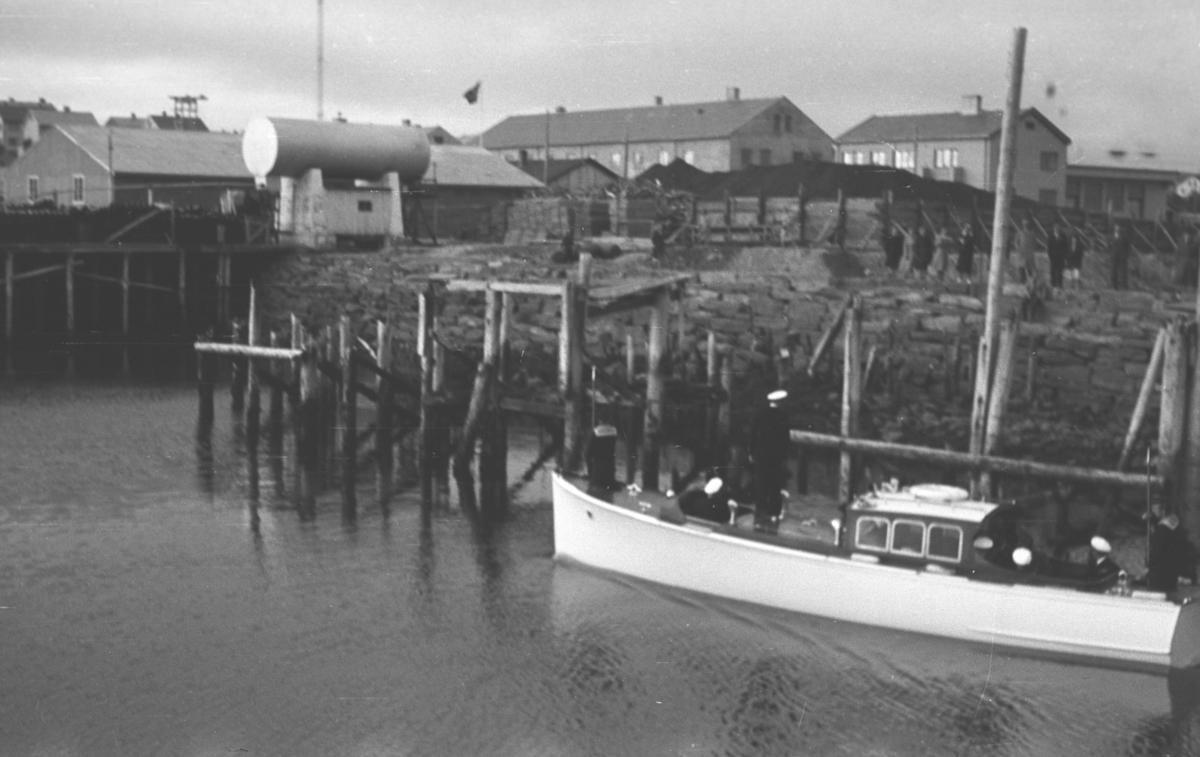 En sjalupp på vei inn mot Vadsøs indre havn. Restene av en kai stikker ut i sjøen på styrbord side av båten.