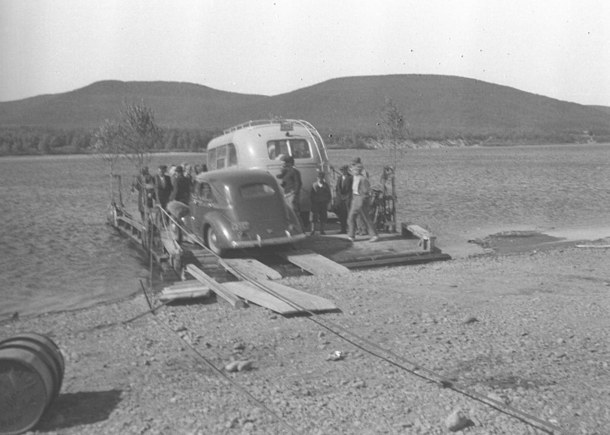 Flere personer, en personbil og en minibuss ombord i kabelferga som gikk over Tana-elva ved Seida. Bussens registreningsnummer er muligens Y-2142, som var en Volvo personbuss, 1939-modell, som tilhørte A/S Polarbil i Vadsø. Polarbil hadde ruter i Øst-Finnmark inkl. Tana.