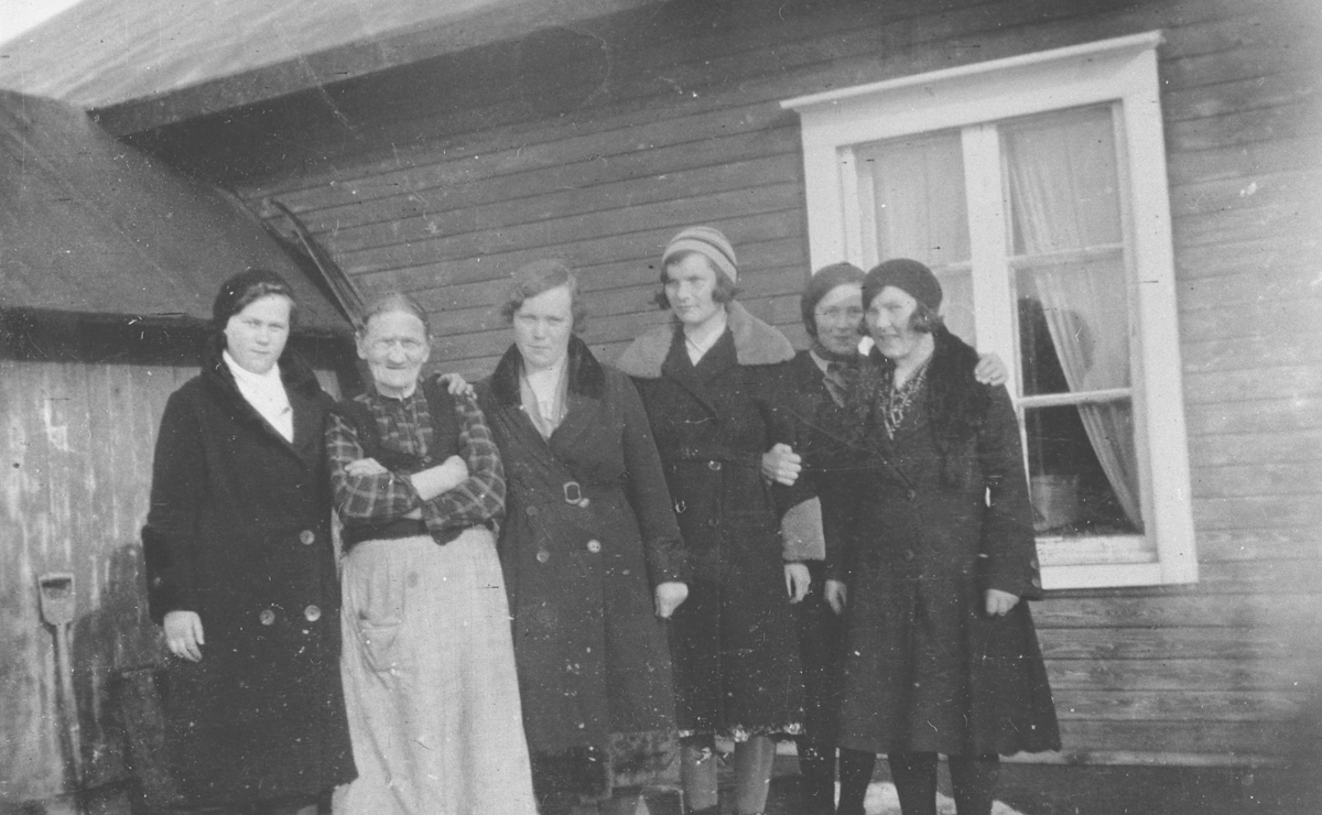 Seks kvinner fotografert ved et hus i Vestre Jakobselv. Kvinnene fra venstre: Emma Reisænen, hennes mor Brita Stina Mietinen (f. Dørmænen i Kuusamo, Finland), Hilda Severine Thuv, Elise Henninen, Miriam Mietinen og Petra Ballo. Kvinnene har vinterkåper på seg. Bildet er antakelig tatt om våren, for det ligger fortsatt litt snø. Bak kvinnene et vindu med lyse gardiner