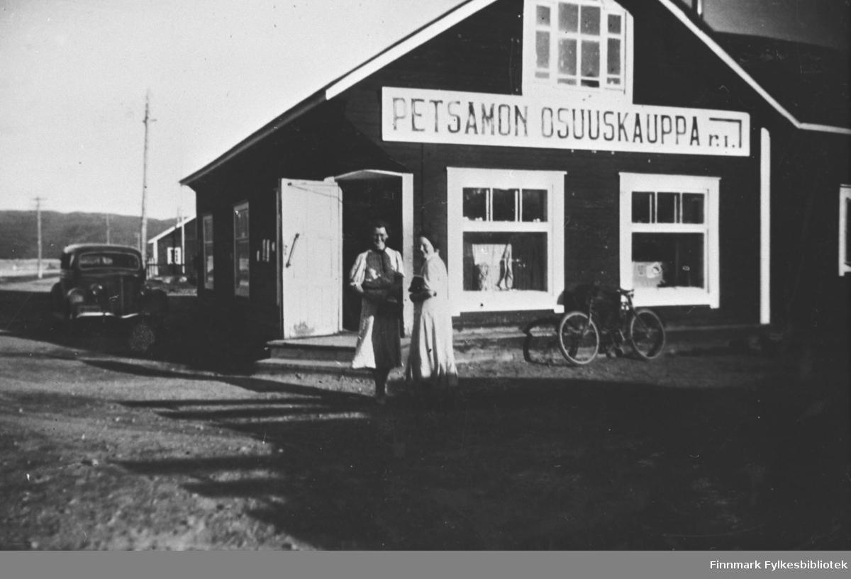Et par fotografert utenfor butikken / kolonialhandelen  i Petsamo / Petsjenga. Biler og sykler står parkert utenfor