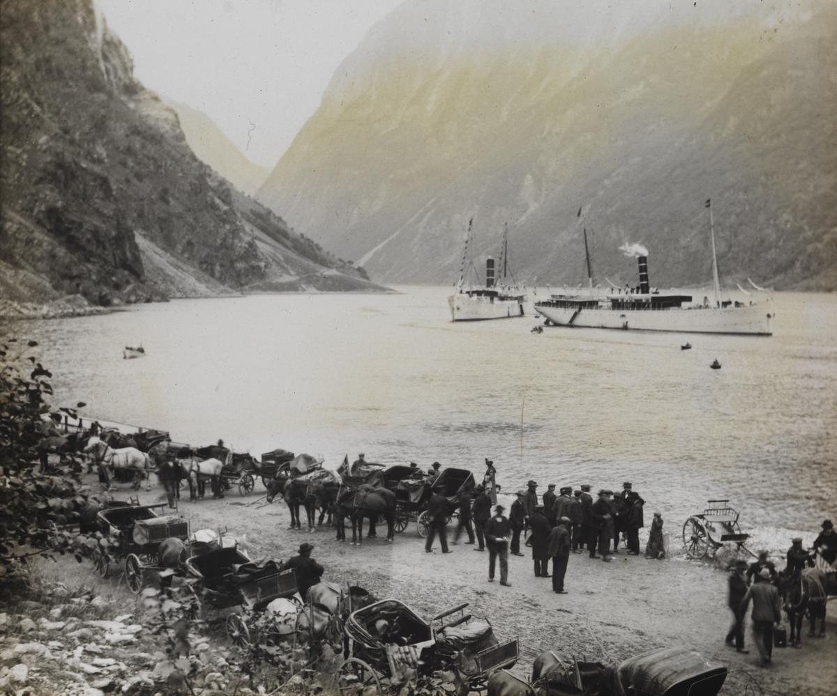 """Dias. Langs bredden av fjorden står en gruppe kvinner og menn, i nærheten står en rekke hester med vogner spent for. På fjorden ligger to mindre passasjerskip, """"Kong Harald"""" og """"Neptun""""."""