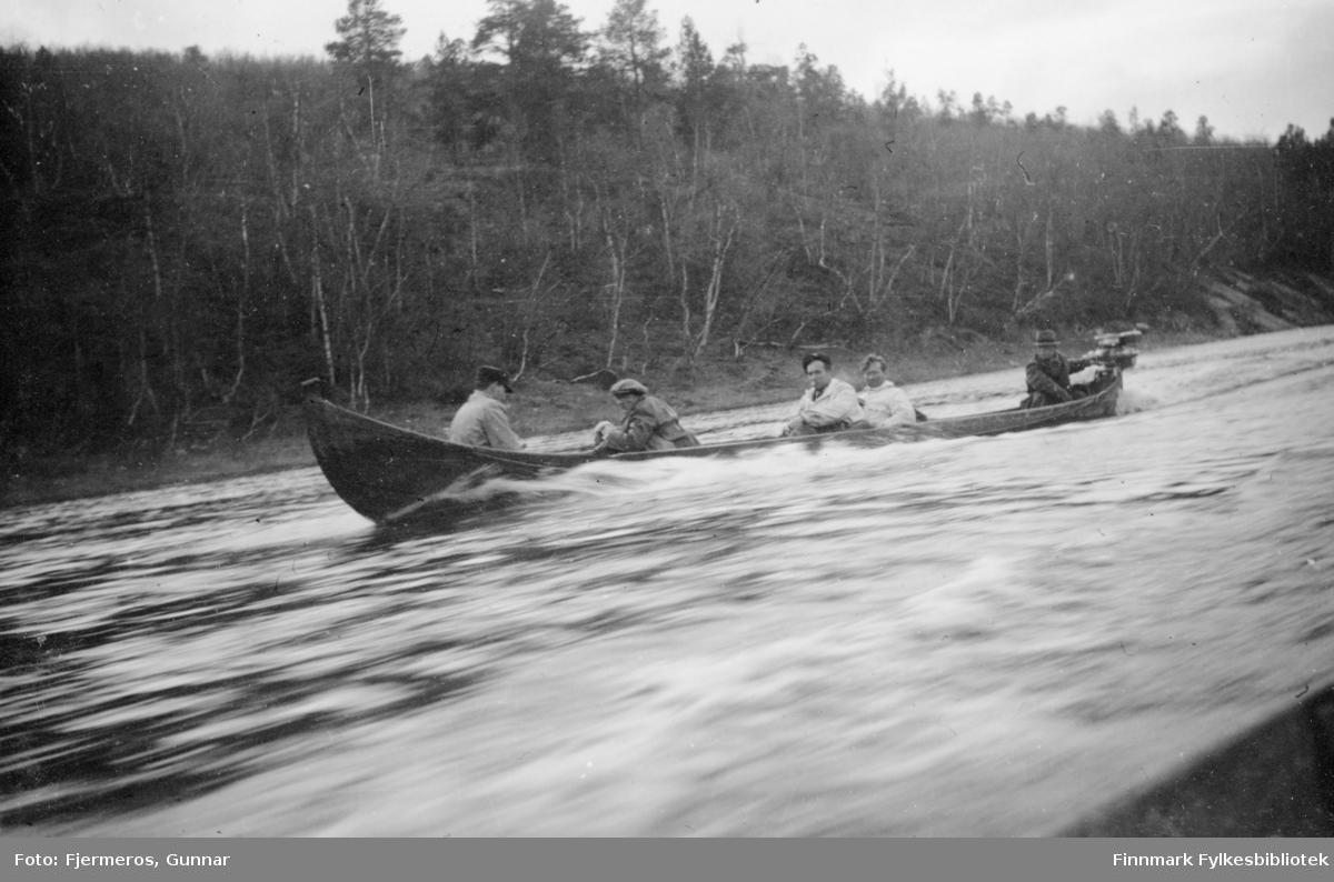 En elvebåt suser av sted på elva Karasjohka. Bildet kan være tatt på en tur fra Bàktemohkenjàrga til Iskuasjohka i mai 1946. Personene ombord er ukjent.