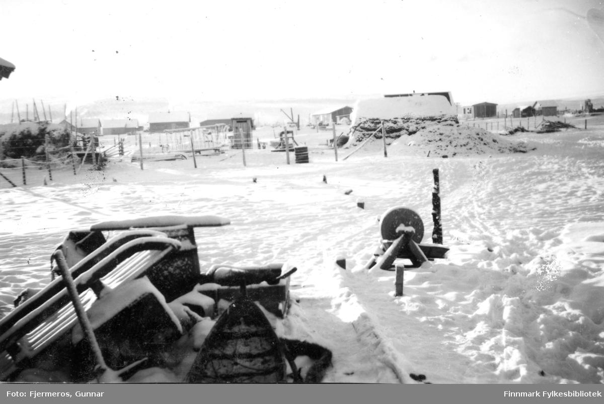 Bilde fra Karasjok en kald vinterdag i 1947. Noen sleder og en slipstein står foran i bildet og noen bygninger på andre siden av jordet.