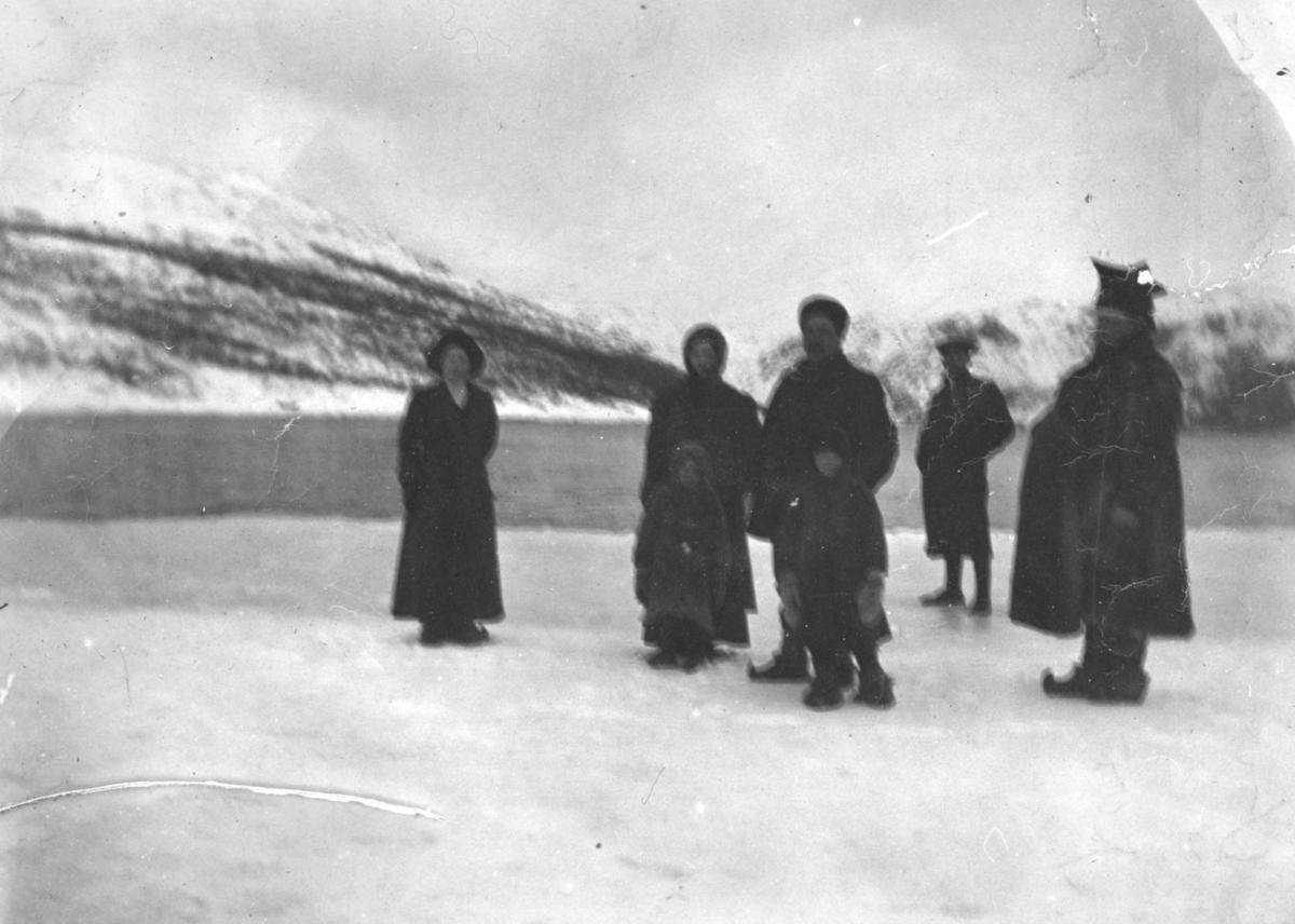 En gruppe folk på isen i Bugøyfjord. Gruppa er kledd i kåper, samekofter og skaller. Mannen til høyre har på seg en samisk lue.
