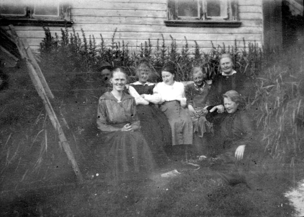 """""""Hos kjøpmann Buch. Hasvik."""" Muligens familien- Buch som poserer for et bilde. Flere kvinner sitter på en benk kledd i kjoler. En mann sitter bak benken. Gruppen er omringet av planter, og bak gruppen kan man se et trehus."""