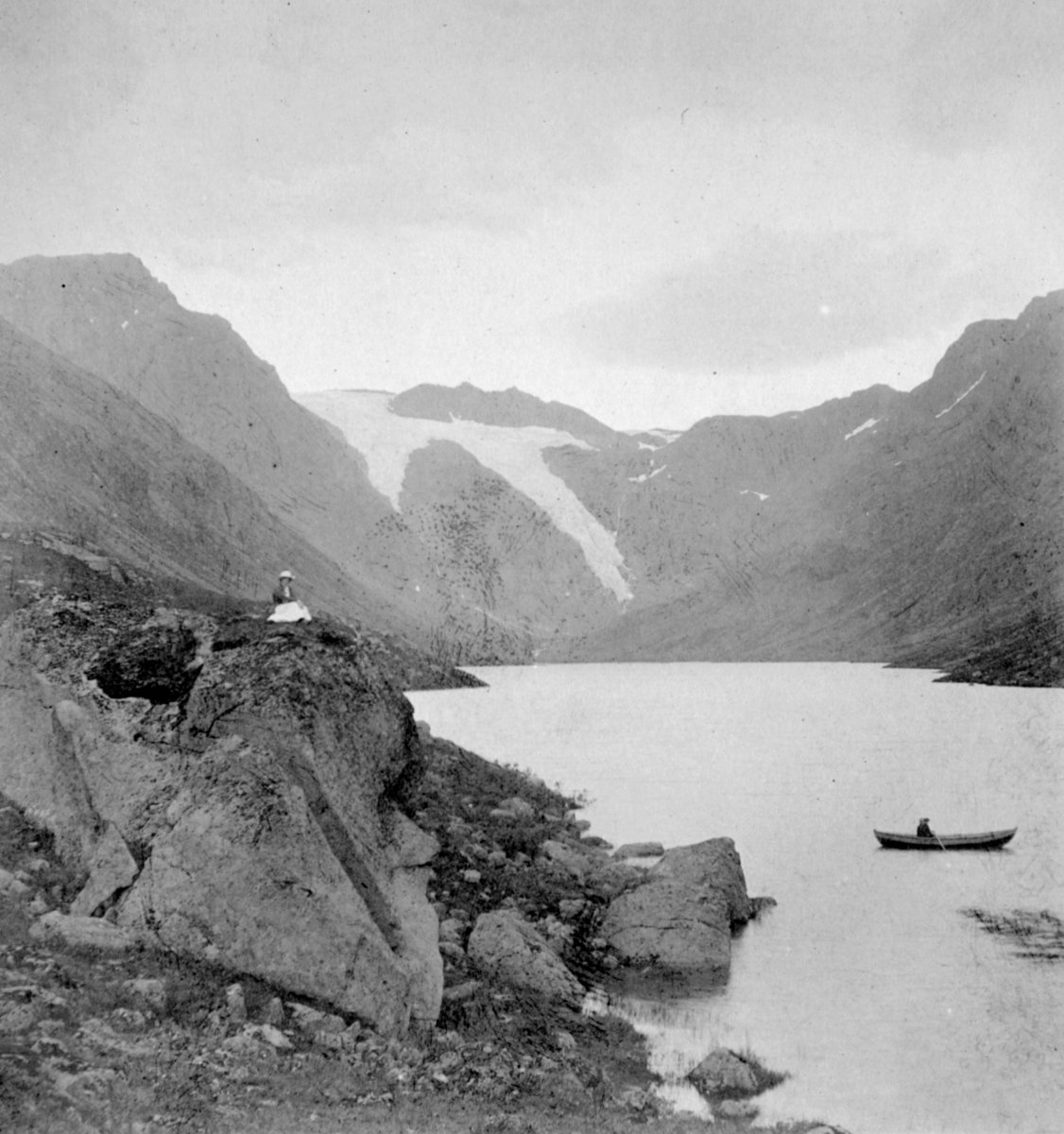 """""""Snebre - Bergsfjord. Finnmark."""" Til venstre sitter en kvinne på toppen av en klippe. Til høyre sitter det en person i en robåt."""