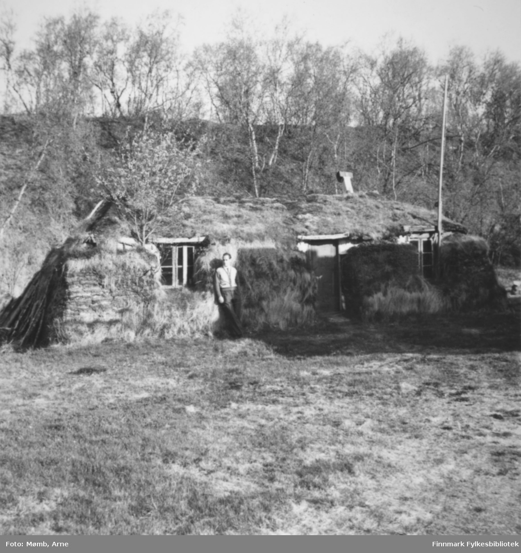 Arne Mømb ved siden gammen til Kristian Rasmussen i Boftsa, Tana 1958. Da tyskerne trakk seg tilbake høsten 1944 og brente det meste i Finnmark, fikk Kristian Rasmussen satt opp denne gammen og familien bodde der til de fikk opp nytt hus etter krigen.