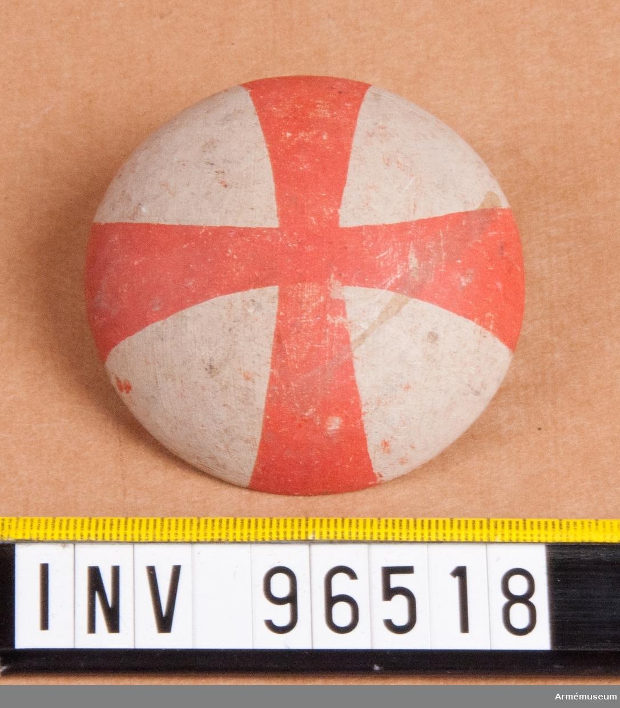 """Regementsmärke som skulle bäras i hatten till 1807 års uniform. Fastställd av Gustav IV Adolf den 5 mars 1807. Rött kors på vit botten. 194 stycken, varav en har texten: """"Svenskt Regements Märke"""" på baksidan."""