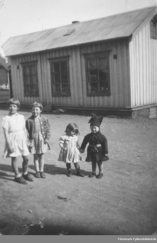 Fire barn poserer for fotografen foran et bygg. Personer og sted er ukjent.