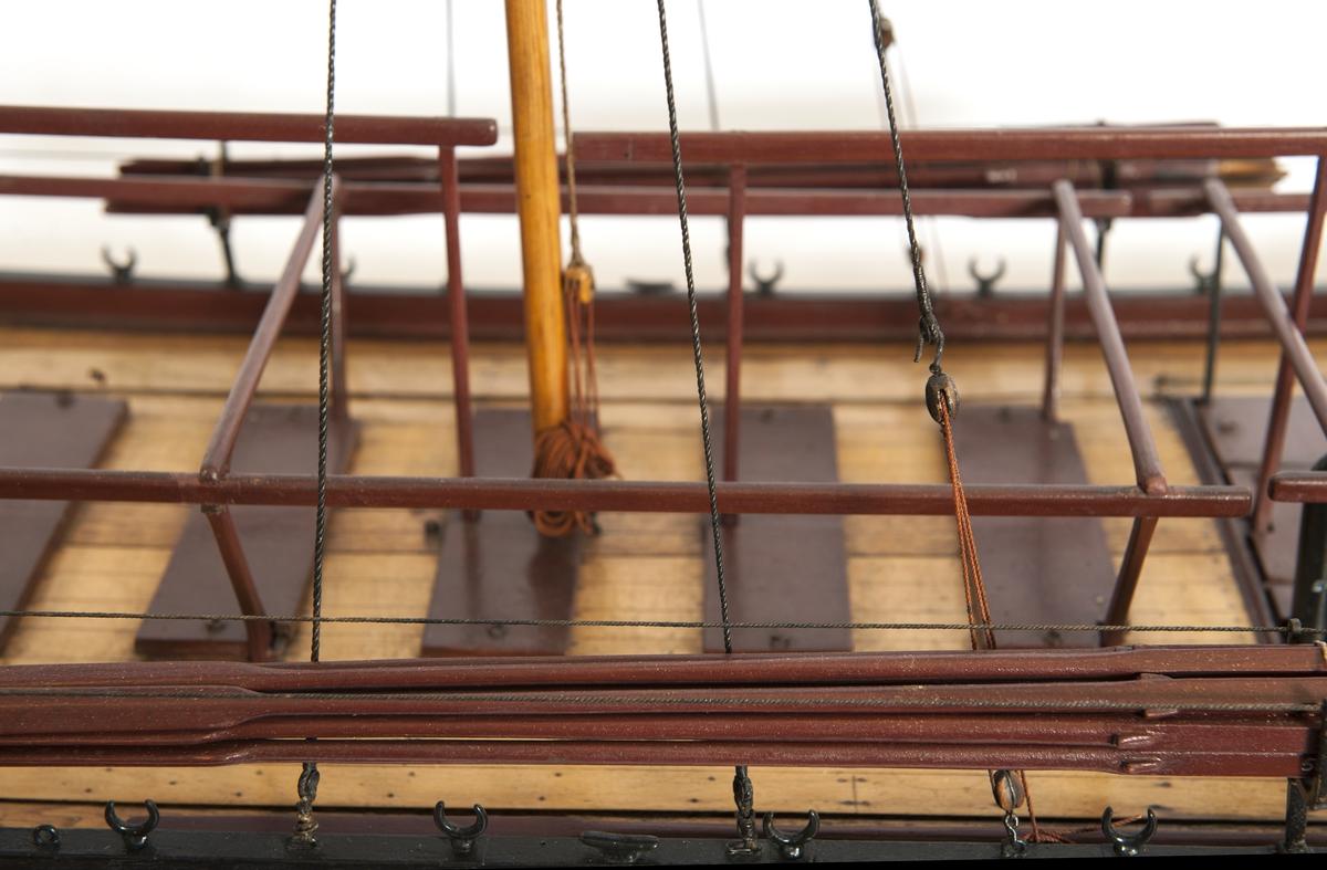 Båtmodell, däckad kanonjolle 1788 års typ. Riggad med två loggertsegel, flagga och spel, vimpel och gösstake. Bordlagd på spant, kravell med inredning. Utdragen akter, tältstomme. 10 par årtullar, 20 st åror, 1 styråra. Roder med rorpinne. Fernissad med svart/vit reling. Bruna åror, däcksluckor och lavetter. 2 träkanoner. 2 fernissade skrå. Nytt skrå 1938. En grov kanon akterut, en nicka förut. En man vid åran. (Skrivet i det gamla kortet för hand: Ritad av A. Wiggman 1826).