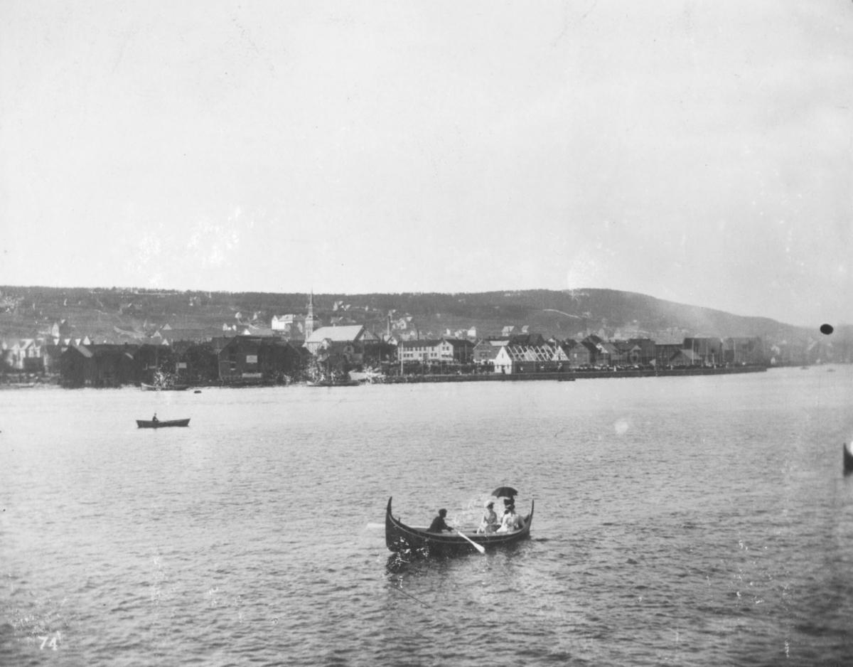 """""""Tromsø."""" I forgrunnen kan man se en mann som ror en båt med to kvinner i. En av damene holder på en parasoll."""