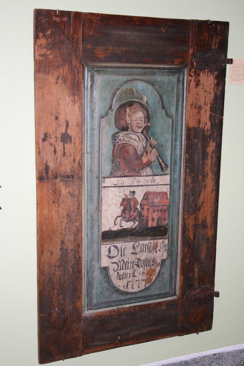 Den ene side mørk brun marmorert, dekorert i speil med kraftige C-ranker  i sort og mørkeblått.  På den annen side  to billedfelt over hverandre: øverst kvinne i fjærprydet hatt med fløyte i hånden, grønn bakgrunn, nedre felt en   rytter foran et høyt toetasjes hus  på hvit bunn, tekst under som nevnt øverst på kortet.  Under fløytespillersken teksten malt:   La Fille veille  = Piken våker.  Antag. fra et fransk stikk.