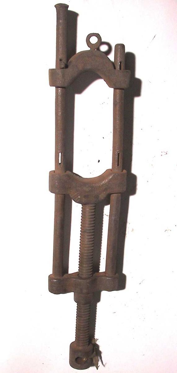 Tvinge. To runde jernstenger med tre tverrgående ledd som binder de to  jernstenger sammen. Gjennom de to øvre bindeledd går en  stang med  skrugjenger, øverst med et gjennomgående hull