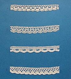 Blått kartongark med fyra stycken prover på skånsk knyppling från Gärds härad. Vid varje prov står en stor bokstav.  4 olika solfjädersvarianter. A. 13 x 1,7 cm, knypplad med 9 par pinnar B. 13 x 1,7 cm, knypplad med 8 par pinnar C. 13 x 1,5 cm, knypplad med 12 par pinnar D. 13 x 1,5 cm, knypplad med 12 par pinnar