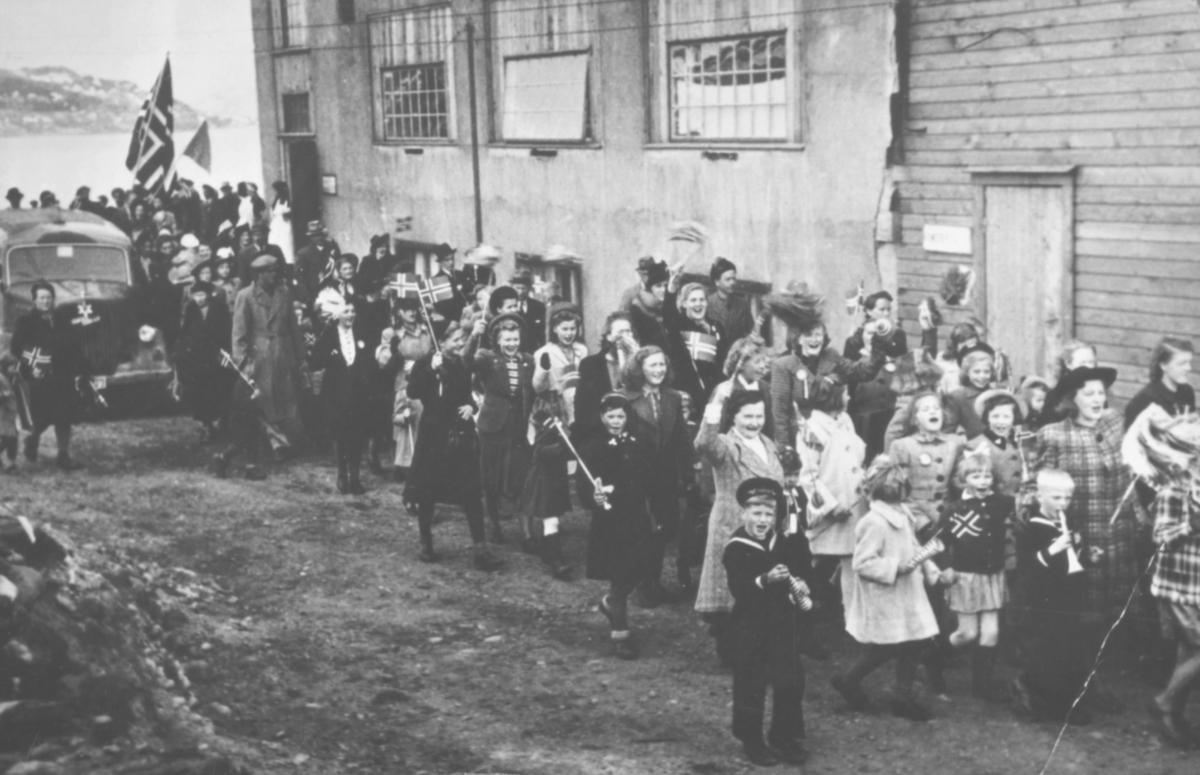 17.mai-tog i Kirkenes, anntagelig etter krigen. Toget passerer en bygning ved sjøen. Det er også en bil på bildet. Barn og voksne - mest kvinner - kledt i finklær.