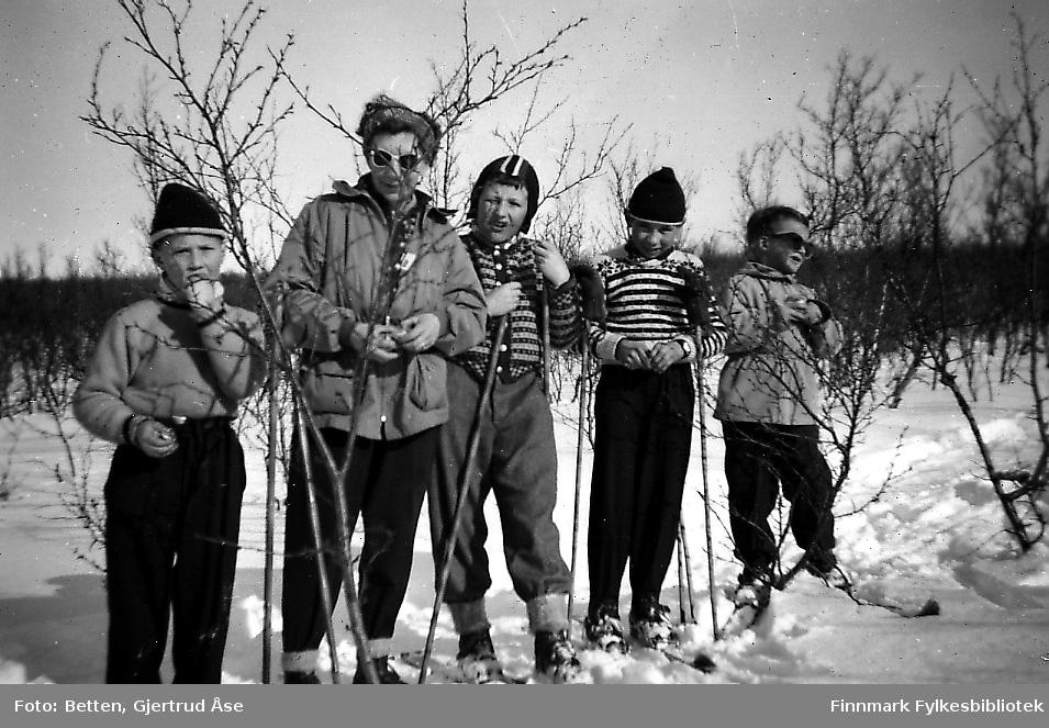 Fire gutter og en kvinne på skitur i Seida en vakker og solig påskedag. Barna er kledd i genserer og luer, en av dem har en norsklue på seg. Kvinner er kledd i skibukser og anorakk. Fra venstre: Rudolf Betten, Åsta Roska (f.Mickelsen ) og hennes sønn Knut, Leif Persen og Bjørn Ottar Betten.