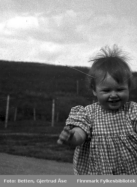 En liten pikebarn kledd i en rutet sommerkjole går ute i sletta en fin sommerdag. Jenten er ca et år gammel og heter Else Gunnlaug Betten (g. Bersvendsen ).