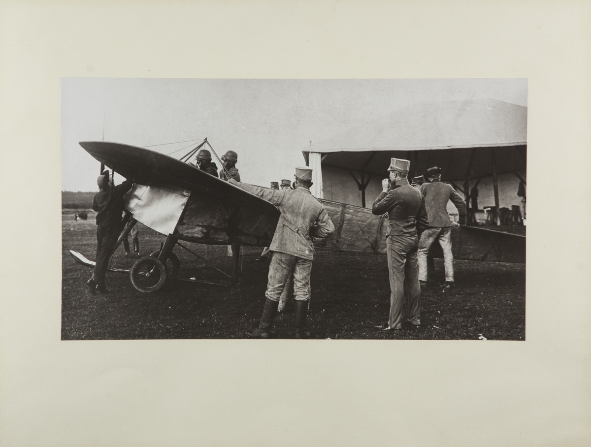 Flygplan M 1 Nieuport vid Axvalla hed. Militärer kring flygplanet. I förarsits sitter Gösta von Porat. Till höger i militärklädsel står Allan Jungner.