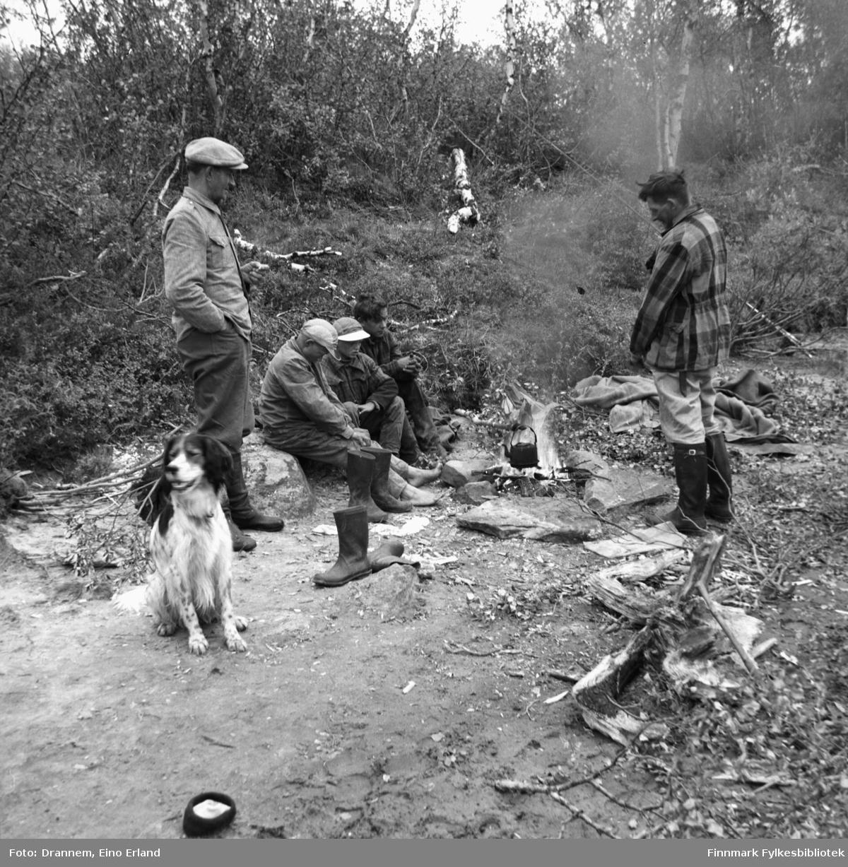 Uuno Lappalainen sammen med tre gutter og en mann (Illippi Gerasemoff) ved bålet i nærheten av grensevakthytta i Näätämö (på finsk side). Rexi hunden holder vakt! Mennene har vært på fisketur.