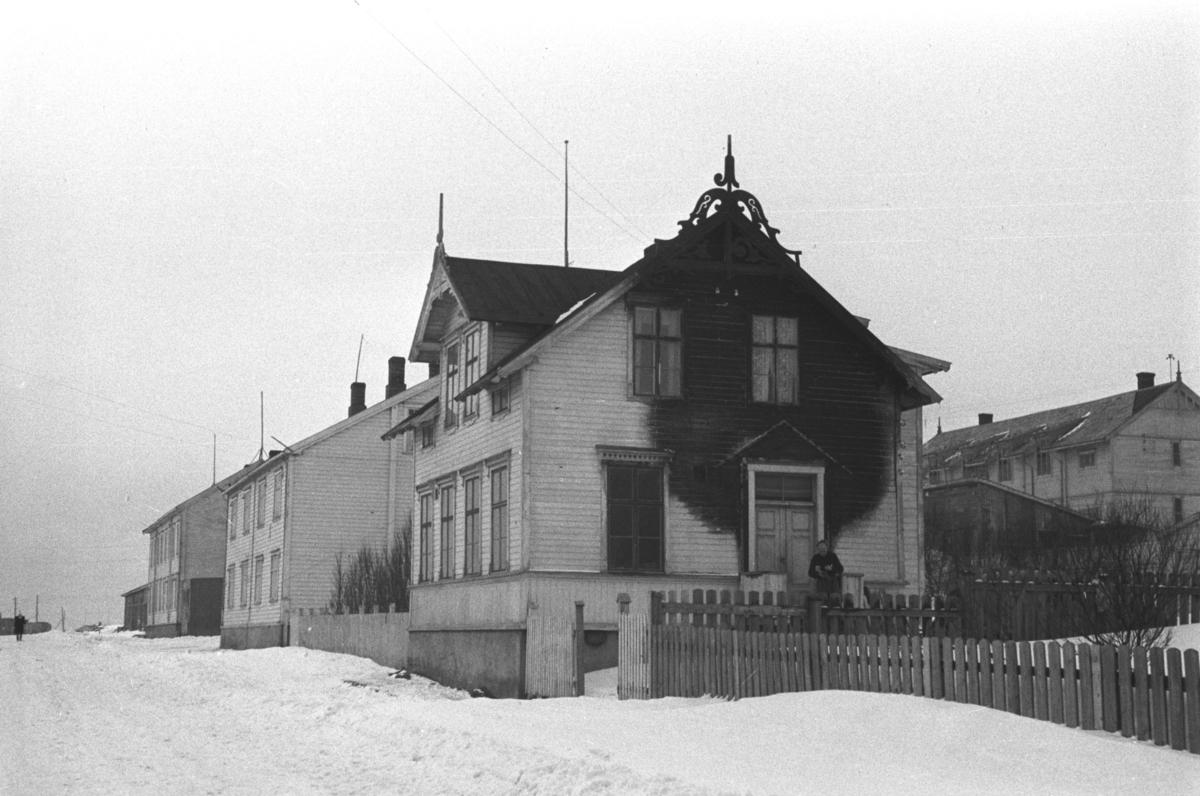 """Et brannskadet hus i Vardø fotografert av arkitekt Ola Hanche-Olsen i påsken 1947 under en tur med Hurtigruta.   Arkitekt Ola Hanche-Olsen arbeidet ved Brente Steders Reguleringskontor i 1946. Hovedadministrasjon for gjenreisning av Nord-Troms og Finnmark ble lagt til Harstad og fikk navnet Finnmark kontoret. Landsdelen Nord-Troms og Finnmark blev oppdelt i syv distrikt med hver sin administrasjon. Honningsvåg, distrikt IV, skulle betjene Nordkapp, Lebesby, Porsanger og Karasjok kommune.  Ola Hanche-Olsen har tatt bildene. Han var født 13. mars 1920 i Borre, død 11. februar 1998 i Gjettum. Han hadde artium fra 1939, arkitekteksamen fra NTH 1946 og arbeidet deretter ved Finnmarkskontoret 1946–48 før han etablerte egen arkitektpraksis. Han debuterte som barnebokforfatter i 1974 med lettlest-boka """"Knut og sjørøverne"""", og skrev i alt 12 bøker.   Han var XU-agent 1944-45, og var også en aktiv fjellklatrer og friluftsmann. XU var den største og viktigste allierte etterretningsorganisasjonen i det okkuperte Norge under andre verdenskrig. Det meste av XUs virksomhet ble holdt hemmelig til 1988. Ola var gift med Solveig Hanche-Olsen (f. Falkenberg); de fikk 3 barn, blant dem matematikeren Harald Hanche-Olsen."""