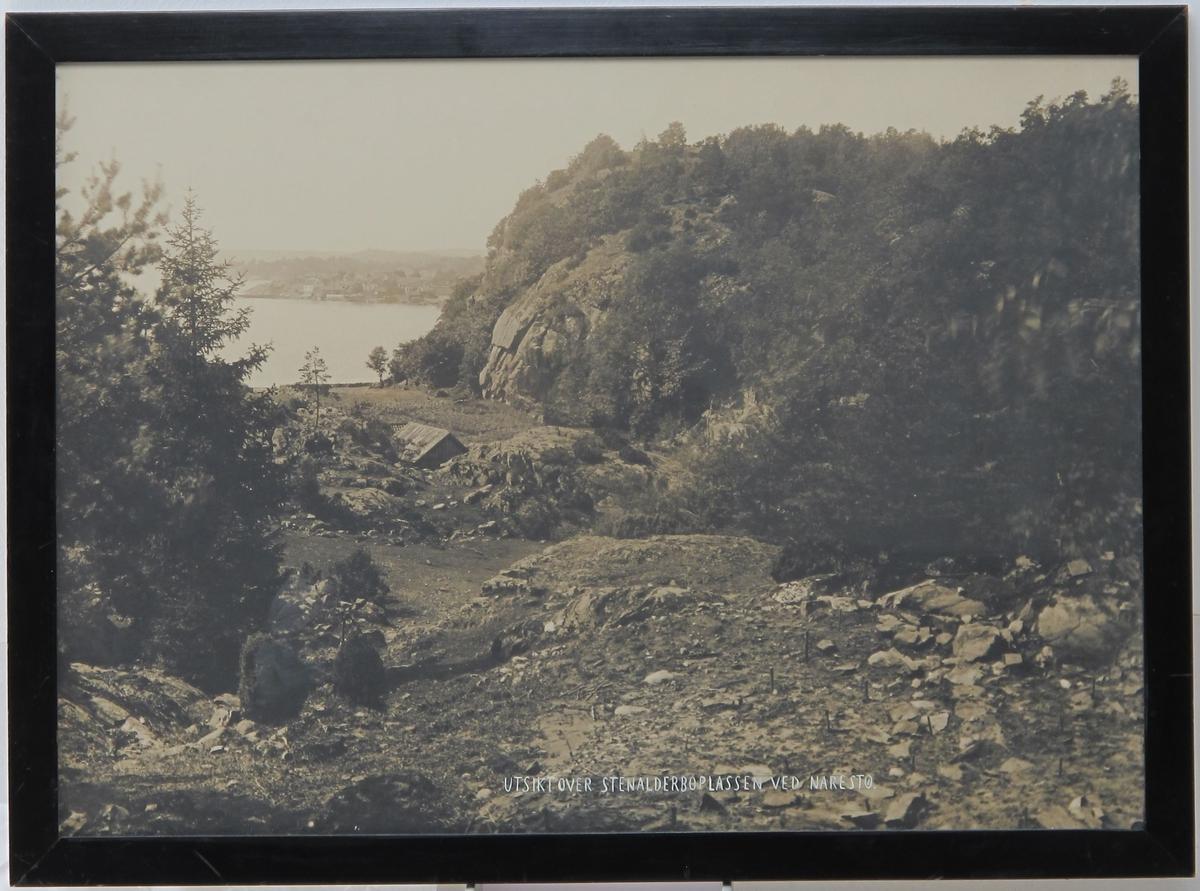 Utsikt over steinalderboplassen i Narestø. Boplassen fra forgrunnen  til høyre og på skrå innover mot venstre,   sjøen i bakgr. Nærmere vannet en potetkjeller med sadeltak. Hei med busker th.