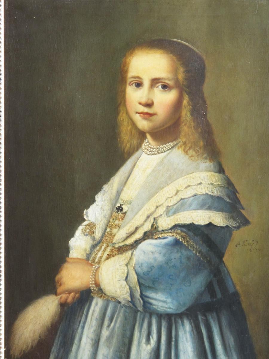 Portrett av pike i blå kjole og med fjær i hånden. Knestykke av venstrevendt pike, hodet halv profil, langt rødbrunt hår med pannebånd. lys blå atlas  kjole med hvit kniplingsbesetning på skulderkappene  og på de hvite høye ansjetter. Holder  hvit fjær i  hånden