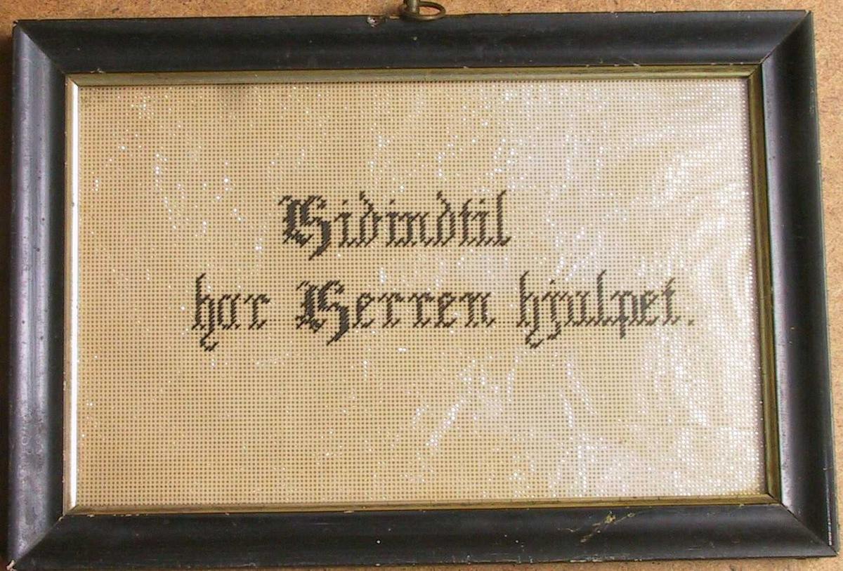 Brodert  skriftsted:  Hidindtil har Herren hjulpet.  Papirstramei med sølvpapir under, tekst i sort.   Sort ramme med forgylt list innerst.