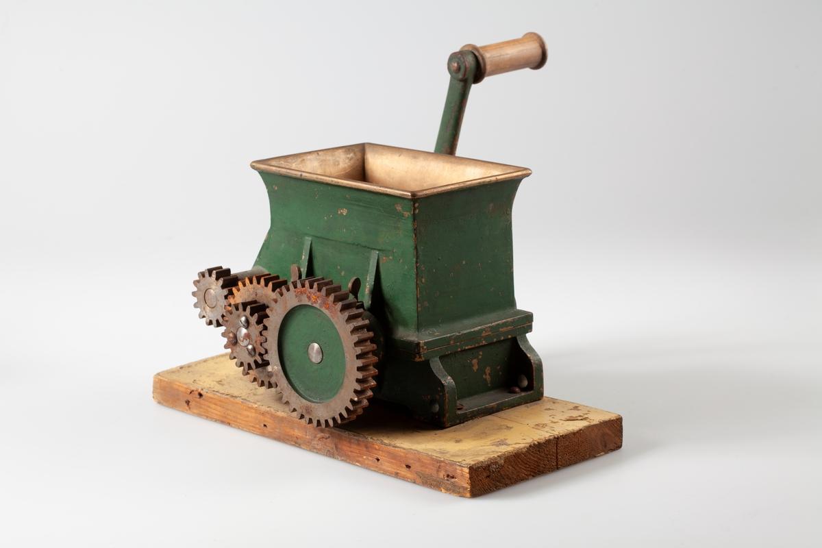A: Kvern med 2 kvernhjul, av bronse. Malt. Fot av jern. Fastskrudd på treplate. Malt overflate. B. Sveiv av jern, med trehåndtak.