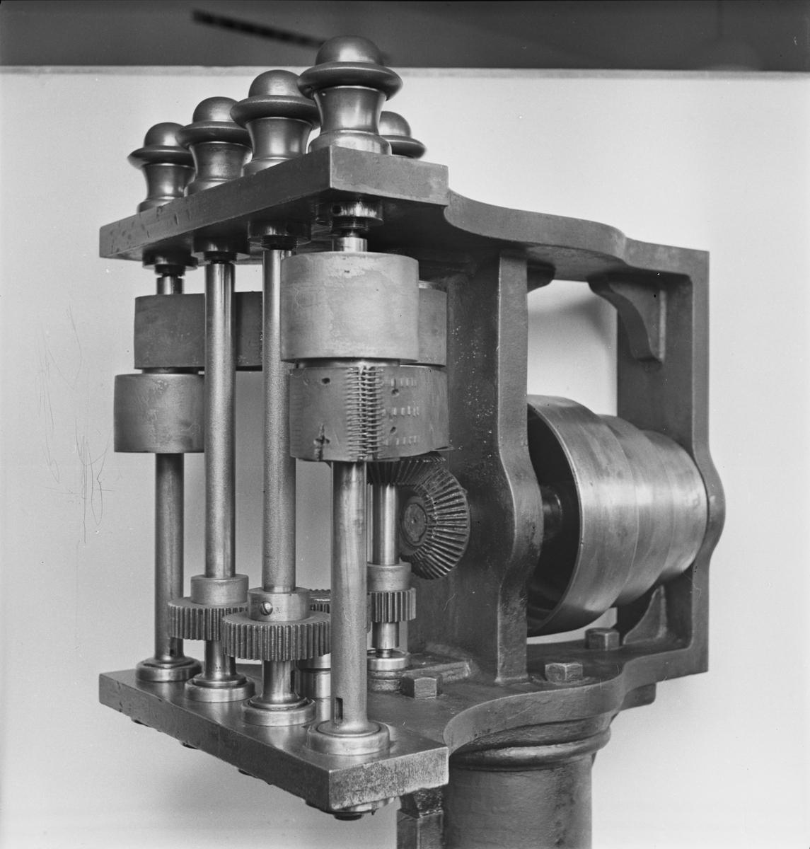"""Fyrspindlig borrmaskin. Etikett, text: """"Fyrspindlig borrmaskin 1869"""". Skylt med """"Köpings M W"""" samt liten bricka med """"91""""."""