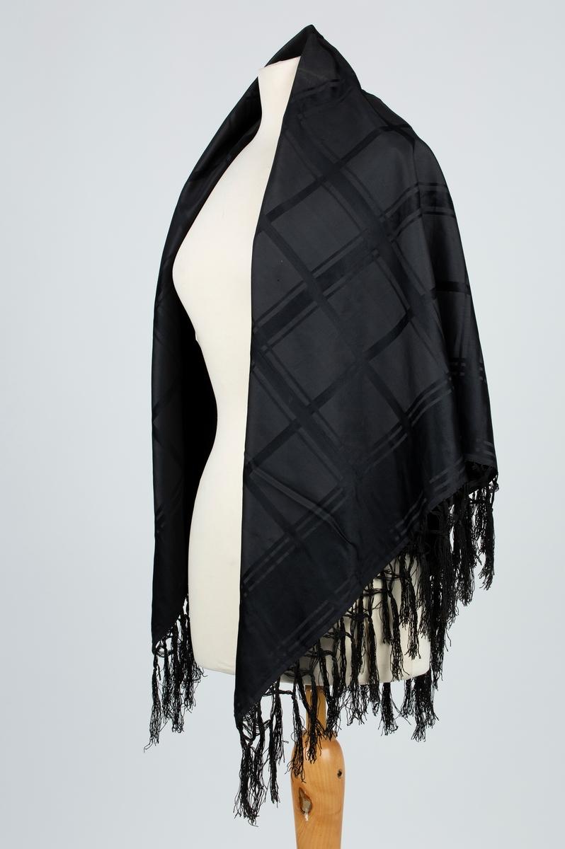 Stort sort silkesjal med frynser. Tilnærmet kvadratisk. Satinvevet. Rutet mønster. Mulig brukt av Amalie eller Anette Gaavim.