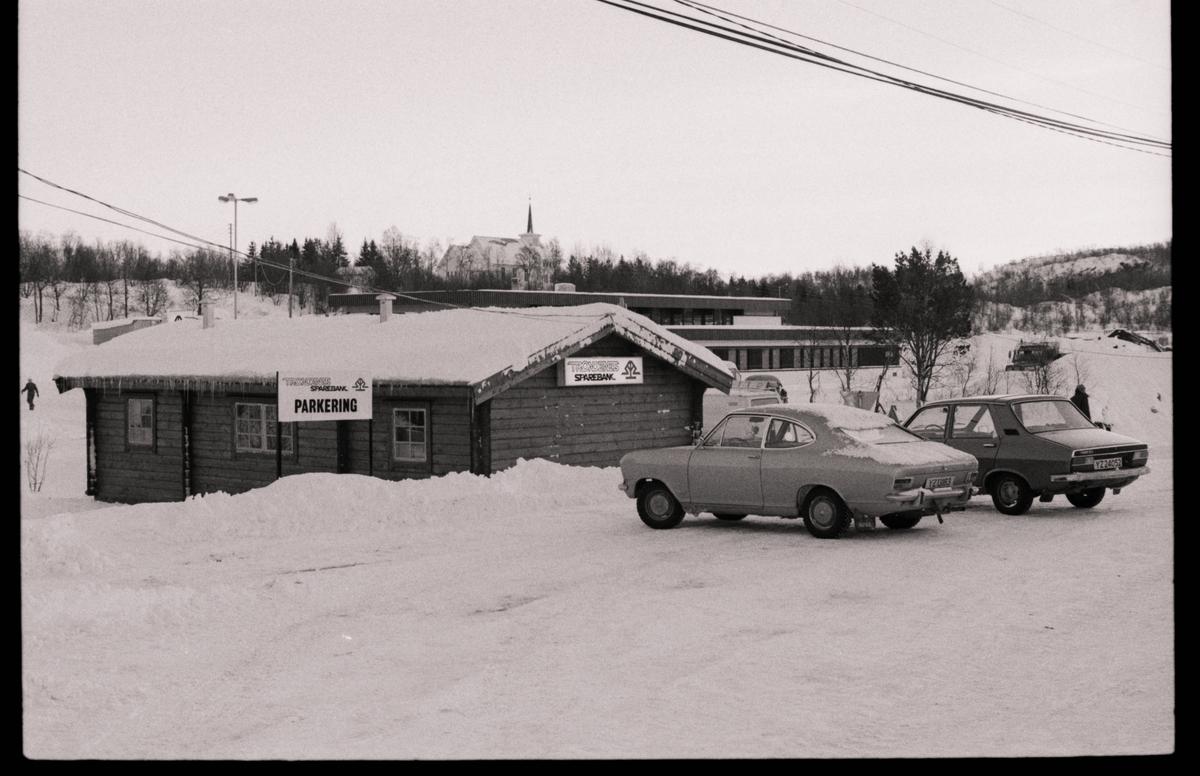 """To biler foran """"bankhytta"""" i Kanebogen. I bakgrunnen biltilsynet og gamle Fredly kirke."""