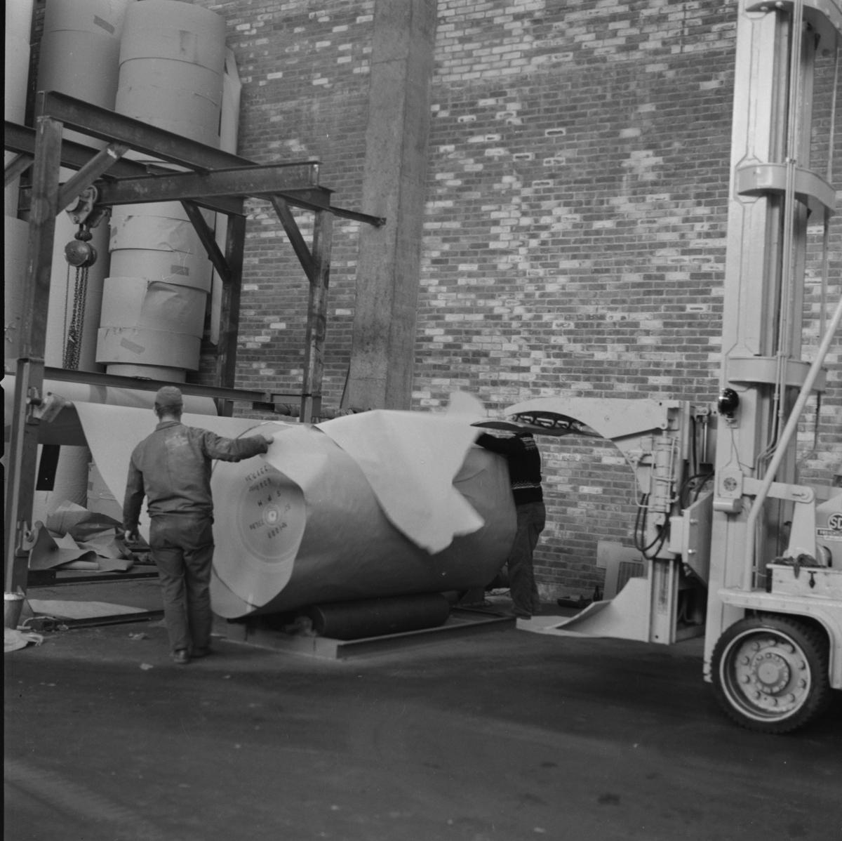 Fra papirfabrikken Sande Papermill. En mann overvåker prosessen. med Stor rull med papir og Truck med gripeklo. Ca. 1960-63