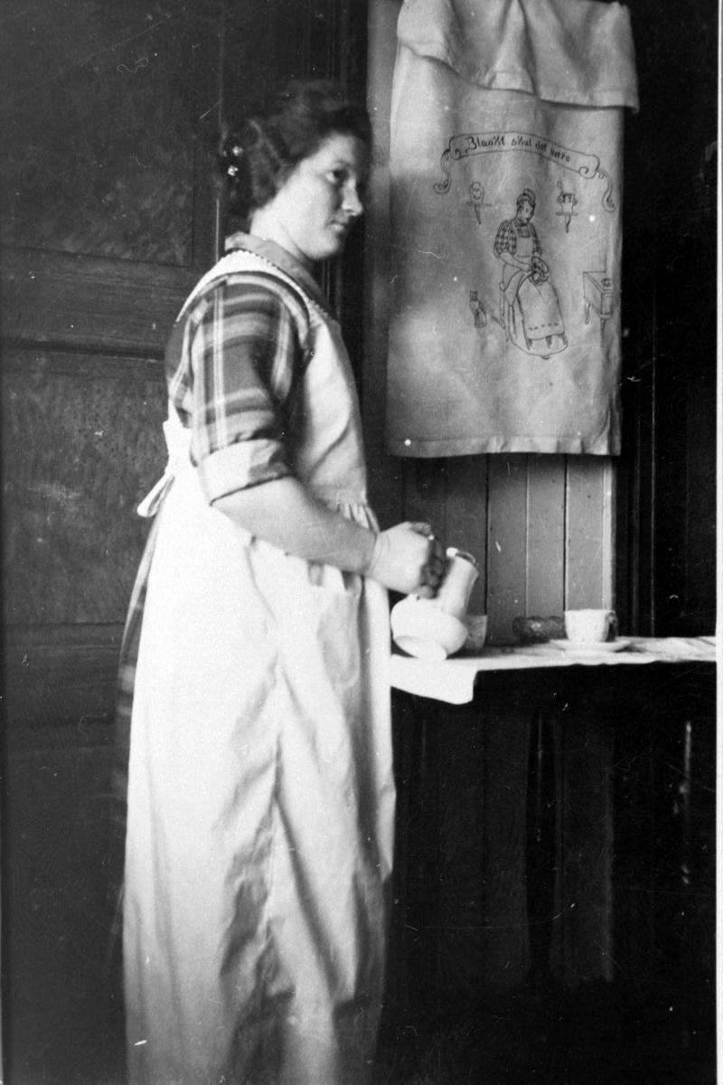 Kvinne skjenker kaffe på et kjøkken.